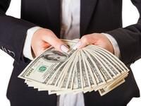 איש עסקים מחזיק בשטרות לאחר הלוואה בערבות המדינה