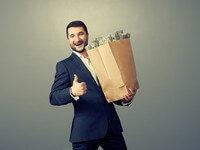 אדם מחזיק שק של כסף ומחייך
