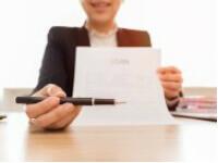 """אישה מחזיקה בטופס הלוואה של 150,000 ש""""ח"""
