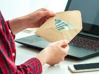 אדם פותח מעטפה עם כסף להלוואה